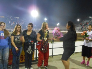 survivor, Rebecca Hultquist hands winner, Talia Feige, a congratulatory bouquet.